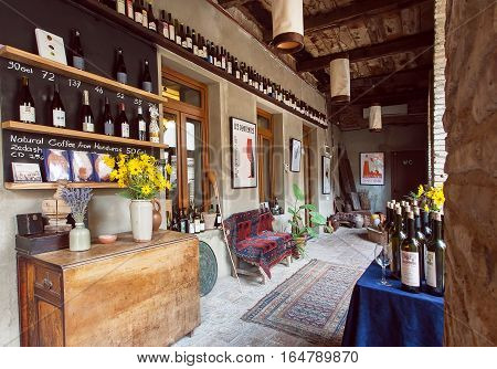 SIGNAGI, GEORGIA - OCT 7, 2016: Vintage furniture and many wine bottles inside the restaurant in old building in the Georgian style on October 7, 2016. Signagi of Kakhetia has a population 2.200
