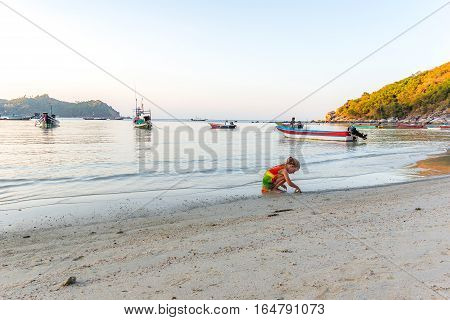 Ao Thong Nai Pan Yai, Koh Pangan, Thailand, April 23, 2016 - Cute little girl plays on the beach a late afternoon with fishing boats in the background