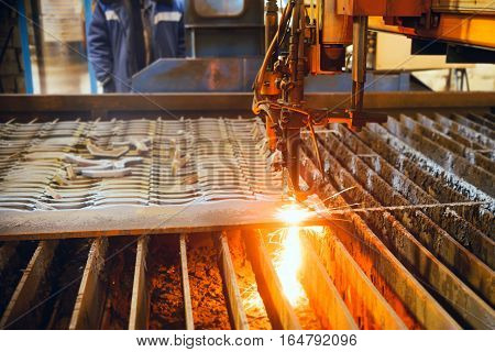 Oxygen torch cuts steel sheet. CNC gas cutting machine. Bright sheaf of sparks of molten metal