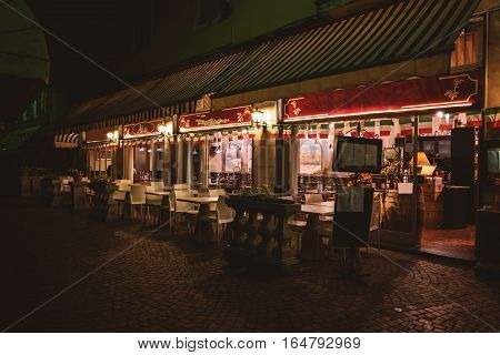 Empty restaurant at night. Tables and chairs near windows. Where to eat in Stresa.
