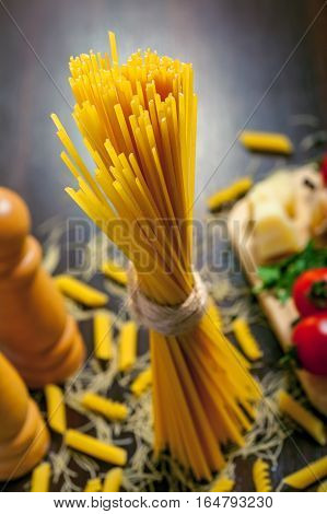 Raw pasta spaghetti with sauce ingredients on table