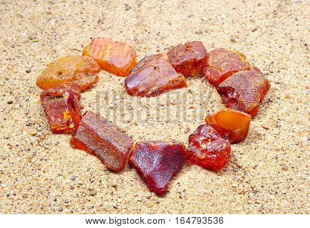 Amber in the shape of a heart in the sand