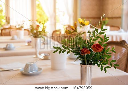 Flowers with leaves in vase. Food joint interior. Varied menu and fast service.