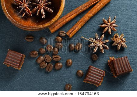 Brown ingredients macro: anise star, cinnamon sticks and chocolate toffee. Top view