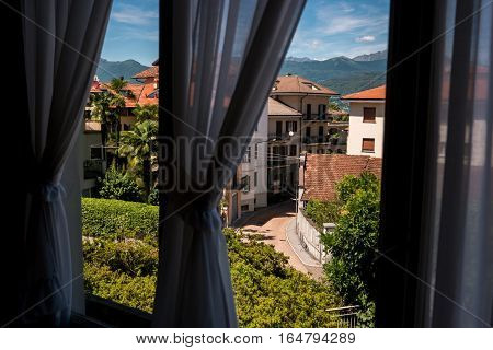 Nature and town behind window. Sky and mountains at distance. View from hotel room.