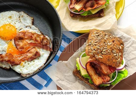 Fried eggs and bacon in cast iron pan and burgers-like sandwiches on paper