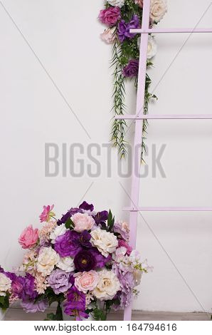 lush bouquet of roses in a flowerpot on the floor beside a decorative ladder