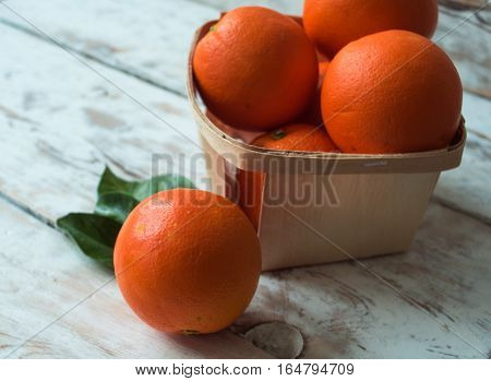 Fresh organic Oranges in basket on wooden table