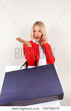 Portrait of young woman in a red jacket with shopping bags on a white background. Woman with shopping bags talking on the phone. Perturbation emotion