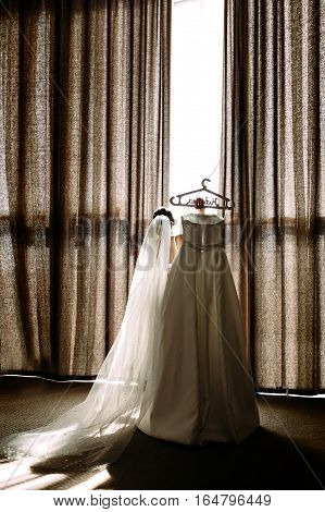 Bride In The Veil Is Holding A Bridal Dress