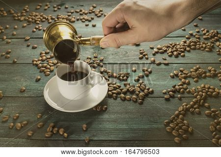 Strong coffee being poured from a vintage coffee pot into a white porcelain cup, on a dark background with scattered coffee beans, toned photo