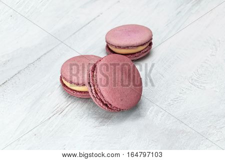 A photo of pink macarons on a pale whitewashed board, with copy space. Selective focus