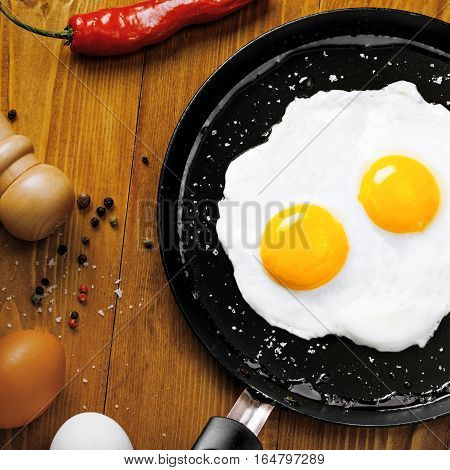 Healthy quick breakfast made of two fried eggs on a table. Traditional simple food on a frying pan for eating. Top view.