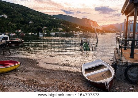 Water, mountains and boats. Rowboat on the shore. Find nice place for fishing.
