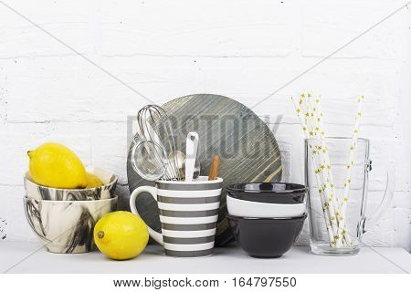 Kitchen stylish modern trend still life monochrome colors, marble bowls, ceramic bowls, gray striped mug, wooden cutting board, juicy fresh lemons, kitchen tools on a background of a white brick wall. selective focus
