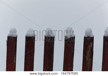 Pickets of an old farm fence with snow cover.