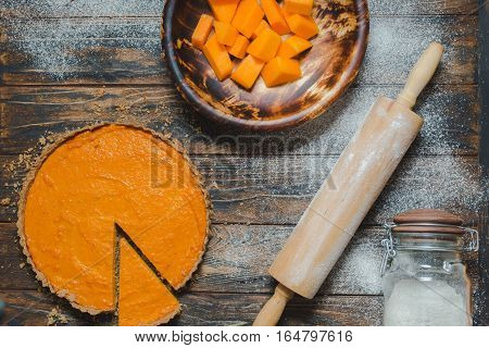 Overhead shot of freshly baked pumpkin pie on rustic brown table. Rolling pin jar and pumpkin pieces in wooden bowl on a side. Spilled flour. Pie slice piece of whole. Healthy food baking cooking in fall harvest Thanksgiving.