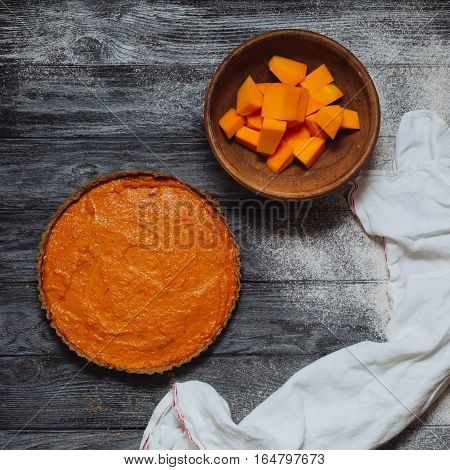 Overhead shot of pumpkin pie and butternut squash pumpkin pieces in clay bowl on background of rustic gray wood planks. Homemade pie cooking in fall harvest Thanksgiving healthy food.