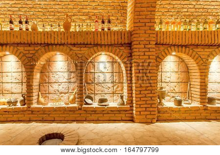 KVARELI, GEORGIA - OCT 3, 2016: Brick walls of old wine cellar Khareba Winery with many bottles in underground cool room on October 3, 2016. The tunnel was opened in 1962 for the World Wine Congress