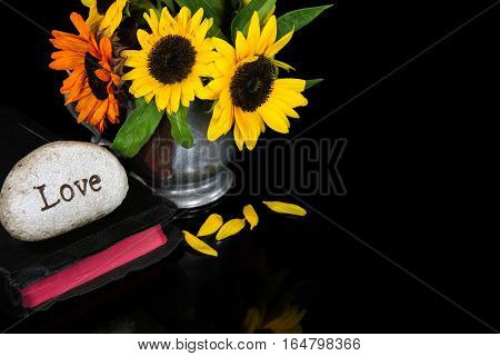 love carved in stone on black Holy Bible with sunflower bouquet in pewter pitcher