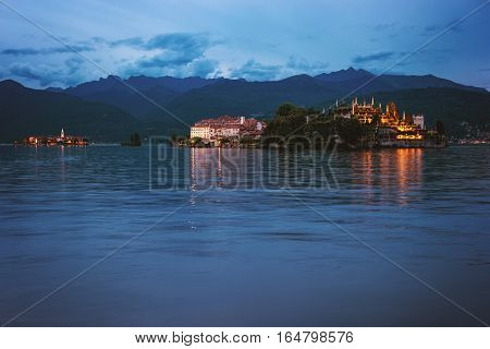 Islands and buildings in evening. Sky, mountains and water. Visit Isola Bella in summer.