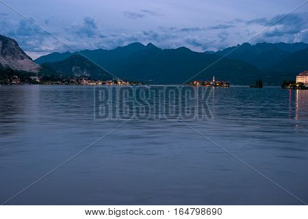 Mountains and town lights. Water and hills in evening. Beauty of Maggiore lake.