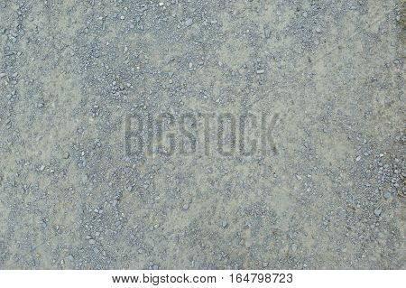 Detail of surface texture with small pebble rock on dirt ground.