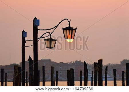 Venice at sunrise lampposts at San Marco squareand risen sun on background Venice Italy. Lampposts from murano glasses are one of the symbols of Venice