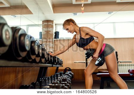 Sexy athlete brunette fitness woman in the gym workout with dumb