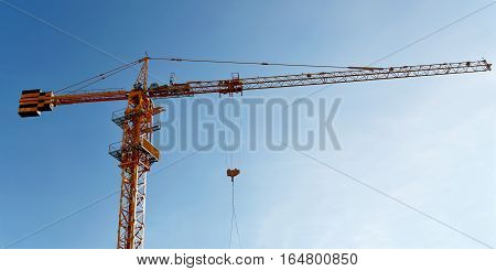 Tower crane on a background of blue sky