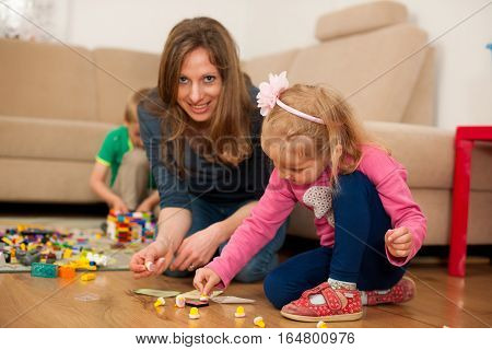 young family plays on a flor in living room