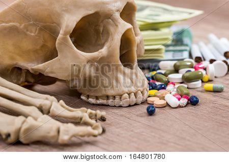 plastic skull of dollars pills drugs and syringes.