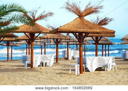 Empty beach in the seaside resort with folded sun loungers and wooden sheds with thatched roof on a background of blue sea waves.