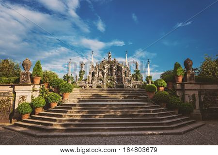Old statues and green plants. Stone stairs in the park. Wonderful garden of Isola Bella.