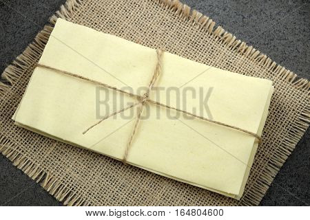 New lasagna sheets tied with twine on a burlap cloth with a dark background.