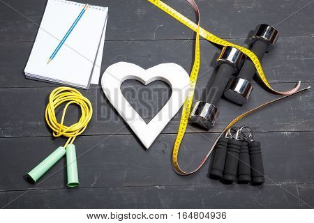 Heart, dumbbells, fitness background on a black wooden background