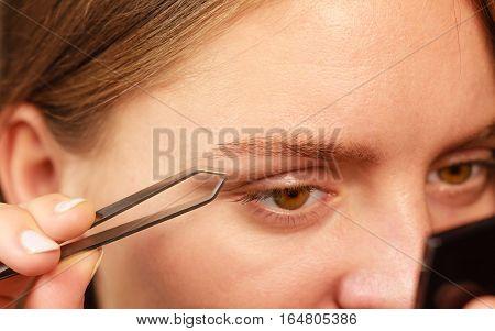 Woman plucking eyebrows depilating with tweezers closeup part of face. Girl tweezing eyebrows.
