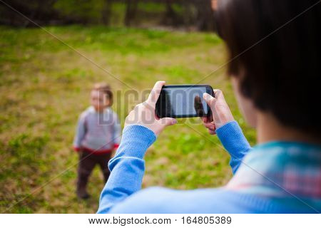 The Girl Makes A Photo Of The Child On The Smartphone.