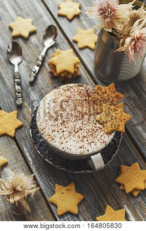 cup of hot cocoa flavored cookies with the stars on a wooden table, selective focus, top view