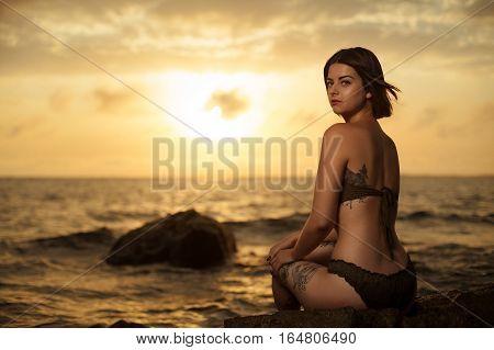 Azerbaijan, Baku - August 10, 2016: Young girl in bikini sitting on a rock on a seaside. Rising sun on the sky with beautiful woman on first plan.