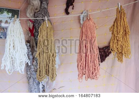 foreground of wool skeins dyed hanging on a rope