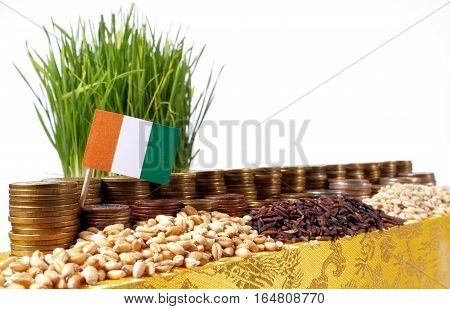 Ivory Coast Flag Waving With Stack Of Money Coins And Piles Of Wheat And Rice Seeds