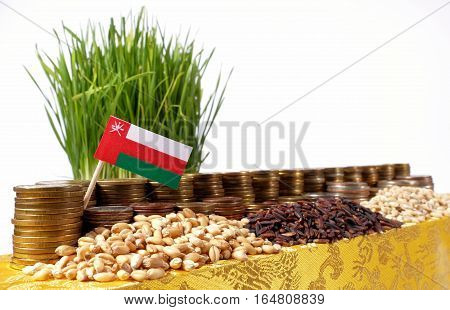 Oman Flag Waving With Stack Of Money Coins And Piles Of Wheat And Rice Seeds