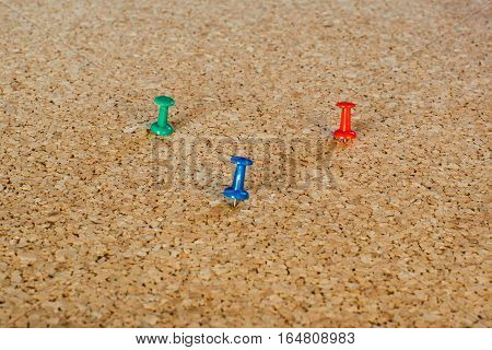 3 coloured thumbtack pins on brown cork pinboard