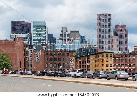 Boston - June 2016, MA, USA: Boston cityscape in a cloudy day, view on skyscrapers and historic old buildings in downtown, cars parked on the bridge above the highway