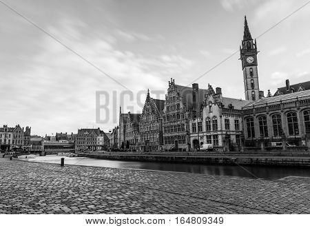 Historic buildings and clock tower in Graslei harbor in medieval Belgian city of Gent (Ghent), black and white photo