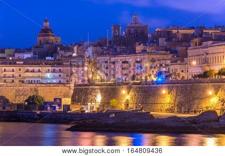 Valletta - December 2015, Malta: Night view of Valletta - the smallest national capital in the European Union, old Church domes and historical buildings reflected in water of the Mediterranean sea