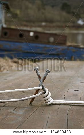 Rustic makeshift mooring bollard with white rope cable old boat in the background