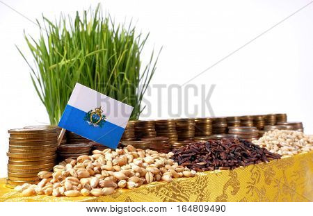 San Marino Flag Waving With Stack Of Money Coins And Piles Of Wheat And Rice Seeds