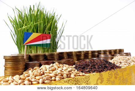 Seychelles Flag Waving With Stack Of Money Coins And Piles Of Wheat And Rice Seeds